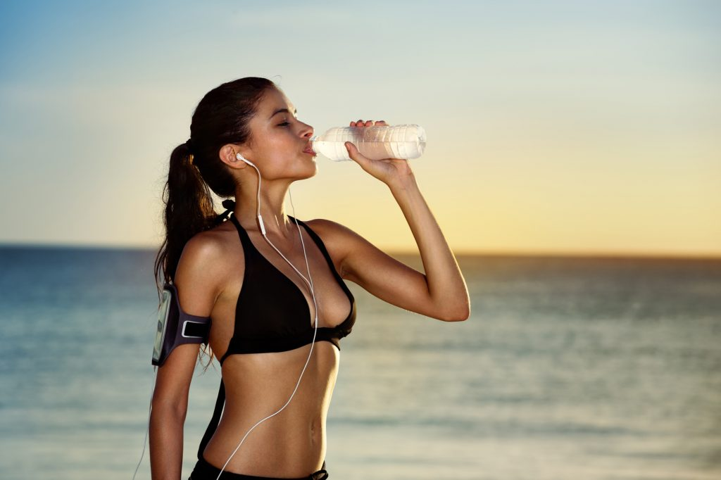 Fitness woman drinking water after exercising on summer day in b