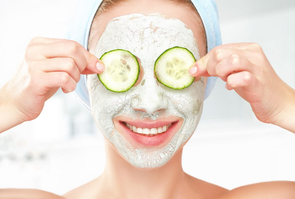 Funny young girl with a mask for skin face and cucumbers
