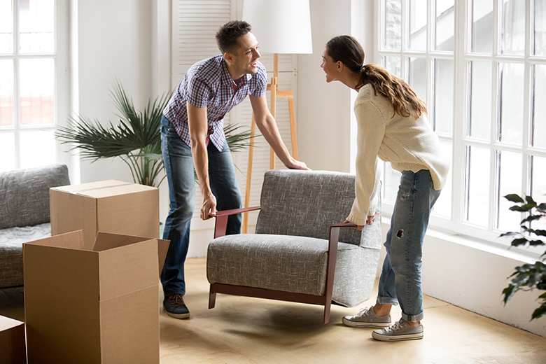Couple carrying chair together, placing furniture moving in new home